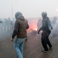 VENICE, ITALY - DECEMBER 14:  'No Global' protesters runs though several tear gas capsules during clashes at an anti-fascist rally on December 14, 2013 in Venice, Italy. There were clashes today between police and protesters as far-right and far-left groups demonstrated near Venice train station.  (Photo by Marco Secchi/Getty Images)