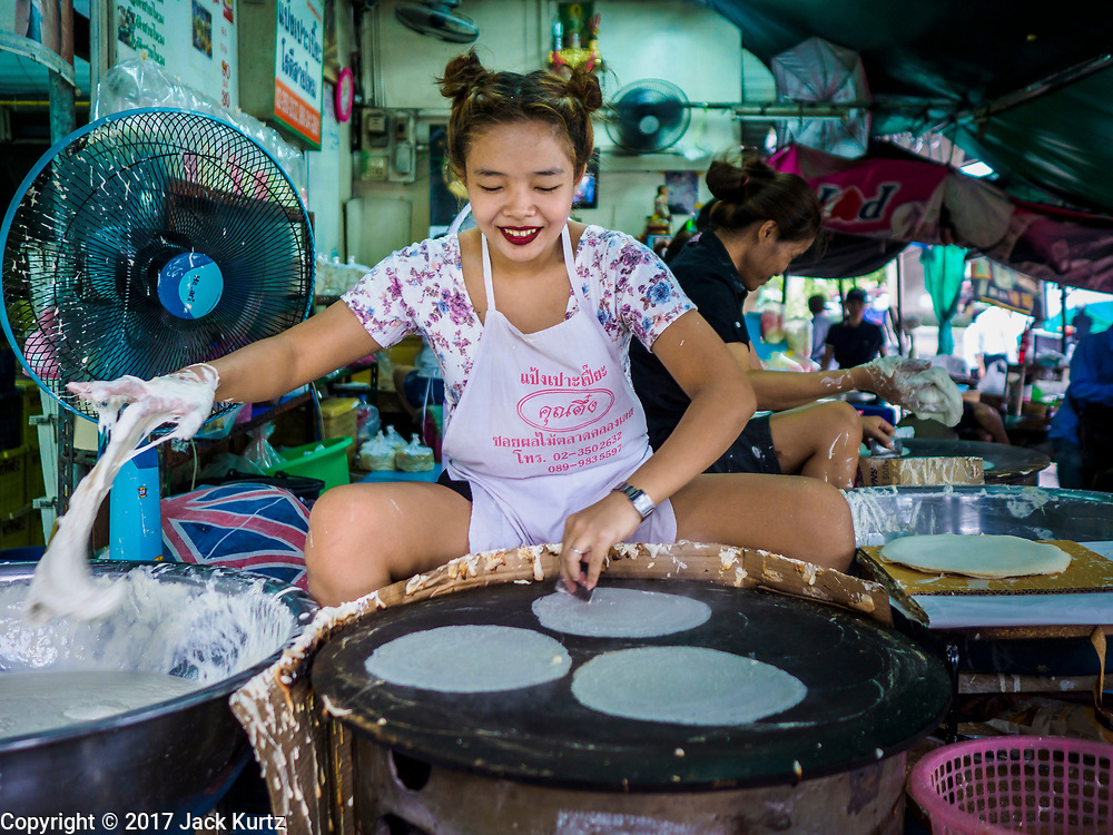 """08 JUNE 2017 - BANGKOK, THAILAND: A woman makes """"roti"""" a type of flat bread, in Khlong Toey Market, Bangkok's main fresh market. Thai consumer confidence dropped for the first time in six months in May following a pair of bombings in Bangkok, low commodity prices paid to farmers and a sharp rise in the value of the Thai Baht versus the US Dollar and the EU Euro. The Baht is surging because of political uncertainty, related to Donald Trump, in the US and Europe. The Baht's rise is being blamed for a drop in Thai exports. This week the Baht has been trading at around 33.90 Baht to $1US, it's highest point in two years.      PHOTO BY JACK KURTZ"""