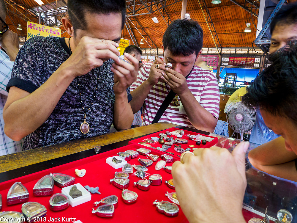 24 DECEMBER 2018 - CHANTABURI, THAILAND: Men shop for amulets in the amulet market in Chantaburi. Chantaburi is the capital city of Chantaburi province on the Chantaburi River. Because of its relatively well preserved traditional architecture and internationally famous gem market, Chantaburi is a popular weekend destination for Thai tourists.  PHOTO BY JACK KURTZ