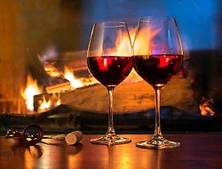 Two glasses of red wine on table at fireplace. Fire, still life, alcohol, drink.