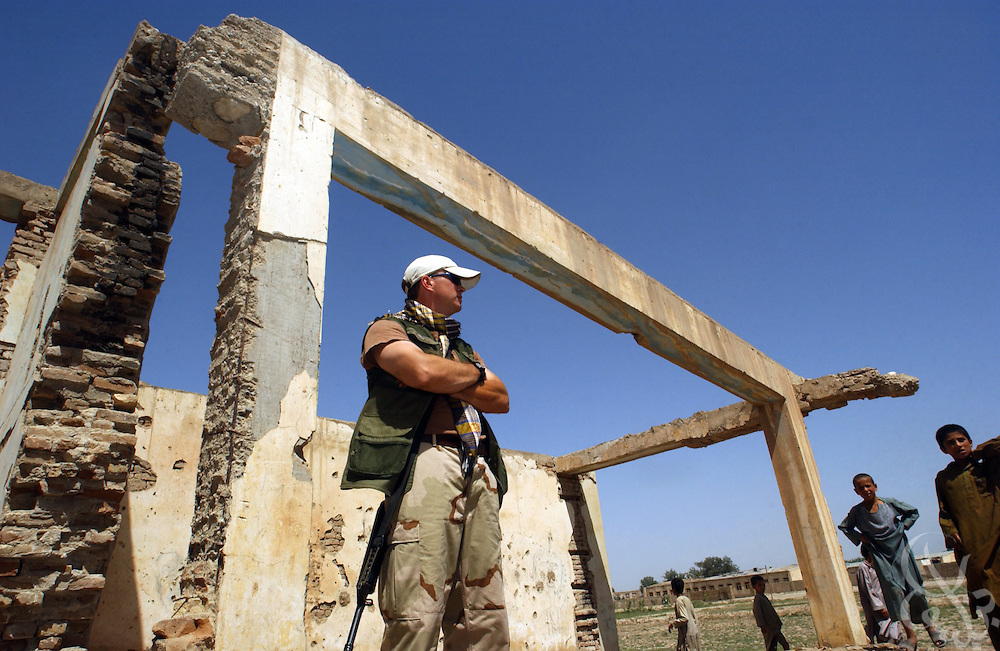 U.S. Army Cpt. Bill Mandrick (R), of the 489th Civil Affairs Battalion from Knoxville, TN, stands among the ruins of the Kunduz Teachers' College June 7, 2002 in Kunduz, Afghanistan. Mandrick and others from the 489th are overseeing the reconstruction and equipping of the school, as well as numerous other humanitarian projects in the area as part of the ongoing Operation Enduring Freedom.