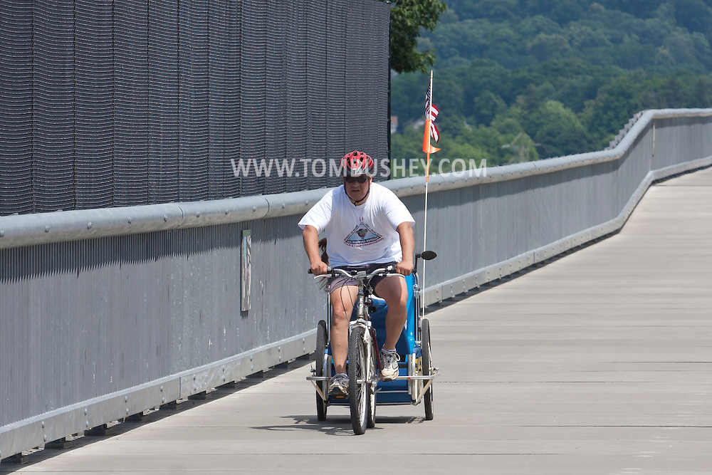 Highland, New York - A man rides a bike with a child in a trailer  across the Walkway over the Hudson on the sunny summer afternoon of June 30, 2014. Walkway Over the Hudson State Historic Park is a linear walkway spanning the Hudson River. At 212 feet tall and 1.28 miles long, it is the longest, elevated pedestrian bridge in the world. The walkway was formerly an abandoned railroad bridge.