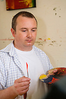 artist with a palette of paint and his knife