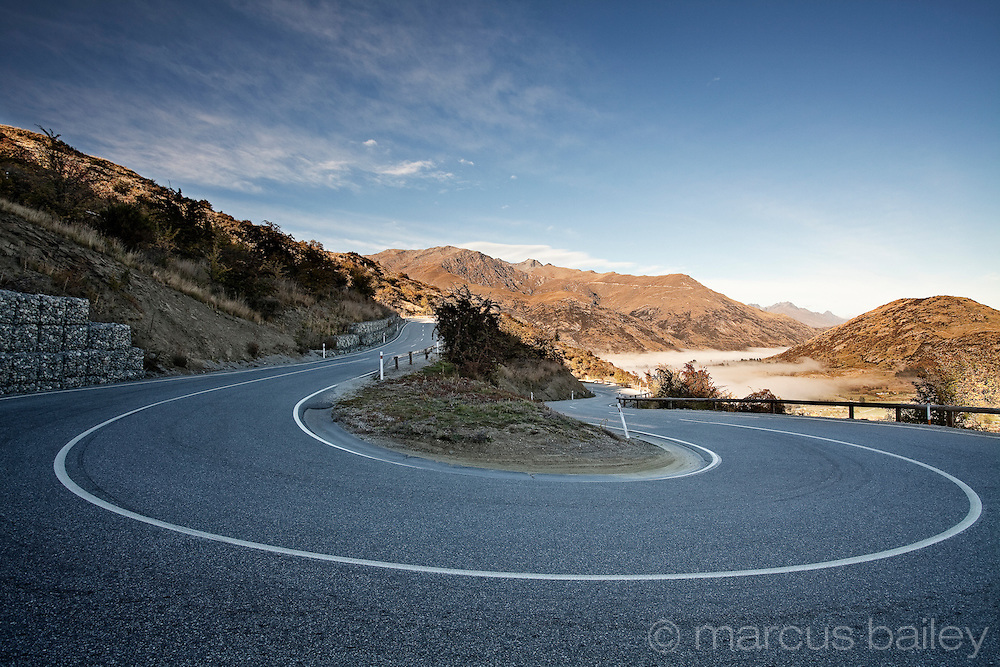 winding road between Queenstown and Wanaka above low clouds across Crown Range, Southern Lakes, Otago, New Zealand