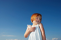 Portrait of young girl (5-6) against blue sky