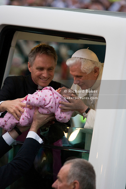 Helped by his personal secretary Georg Gänswein, Pope Benedict XVI kisses a baby lifted up to his open car window as he arrives in his Popemobile. Greeted by crowds in Hyde Park during his papal tour of Britain 2010, the first visit by a pontiff since 1982. Taxpayers footed the £10m bill for non-religious elements, which largely angered a nation still reeling from the financial crisis. Pope Benedict XVI is the head of the biggest Christian denomination in the world, some one billion Roman Catholics, or one in six people. In Britain there are about five million Catholics but only a quarter of Catholics regularly attend Sunday Mass and some churches have closed owing to spending cuts.