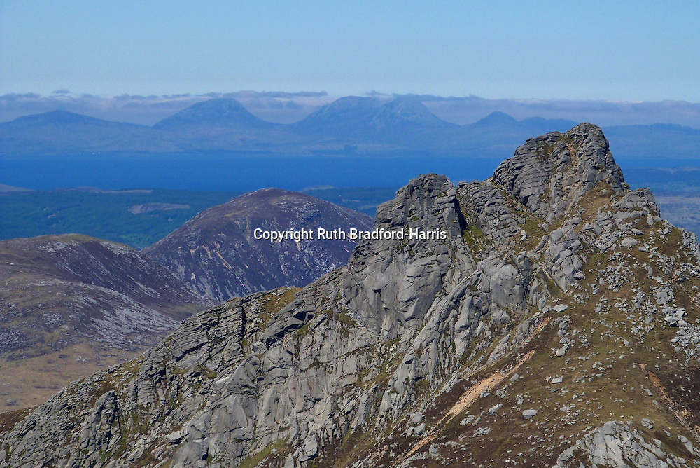 A view of the summit tors of the jagged North Goat Fell from the summit of Goat Fell. Beyond, seen in remarkable detail, are the distant Paps of Jura and other peaks of the Isle of Jura.<br />