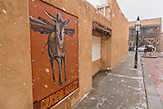 Mural for Burro Alley once known for brothels and saloons in the old west during a winter snow in Santa Fe, New Mexico. Before automobiles almost all goods were transported into the mountain town by pack animals.