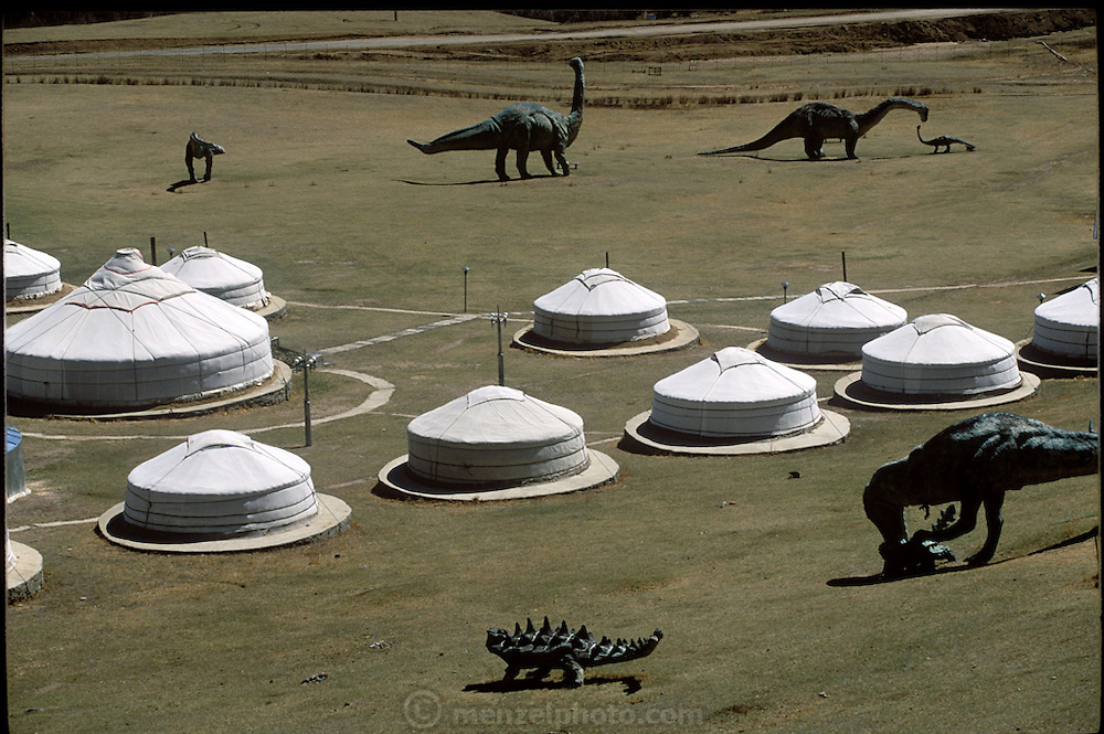 Gers (canvas and felt covered temporary houses of indigenous Mongolian people) and dinosaurs built and placed, in hopes of tourist influx outside Ulaanbaatar, Mongolia. (Supporting image from the project Hungry Planet: What the World Eats.)