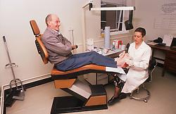 Female chiropodist working on elderly client's feet,