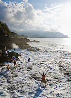 Tourists holding on to the rocky shore as a surprise big wave completely washes over the Queens bath near Princeville on the North shore of Kauai, Hawaii, USA.