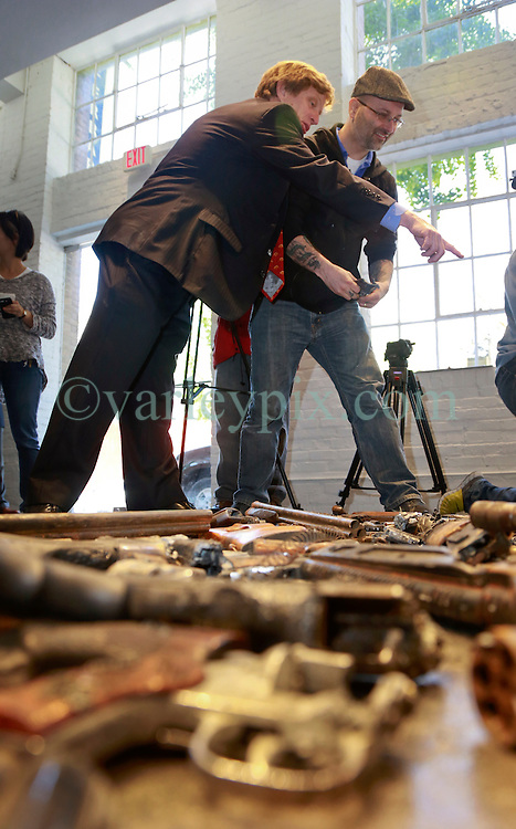 16 April 2014. Jonathan Ferrara Gallery, New Orleans, Louisiana. <br /> Guns in the hands of artist Dan Tague and lawyer Vincent Booth (L - pointing) at the Jonathan Ferrara Gallery to announce the 'Guns In The Hands Of Artists' project where artists take parts from 190 destroyed weapons acquired by the New Orleans Police department through a buy-back program and convert them into art.  <br /> Photo; Charlie Varley/varleypix.com