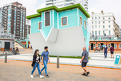 © Licensed to London News Pictures. 18/05/2019. Brighton, UK.  Members of the public visit the upside down house as the newest addition on the Brighton and Hove promenade. Photo credit: Hugo Michiels/LNP