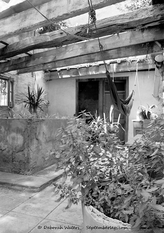 Can Masdeu, Barecelona, Spain 2004: derelict old bath house turned patio area with hammock swinging from broken roof beams above plants