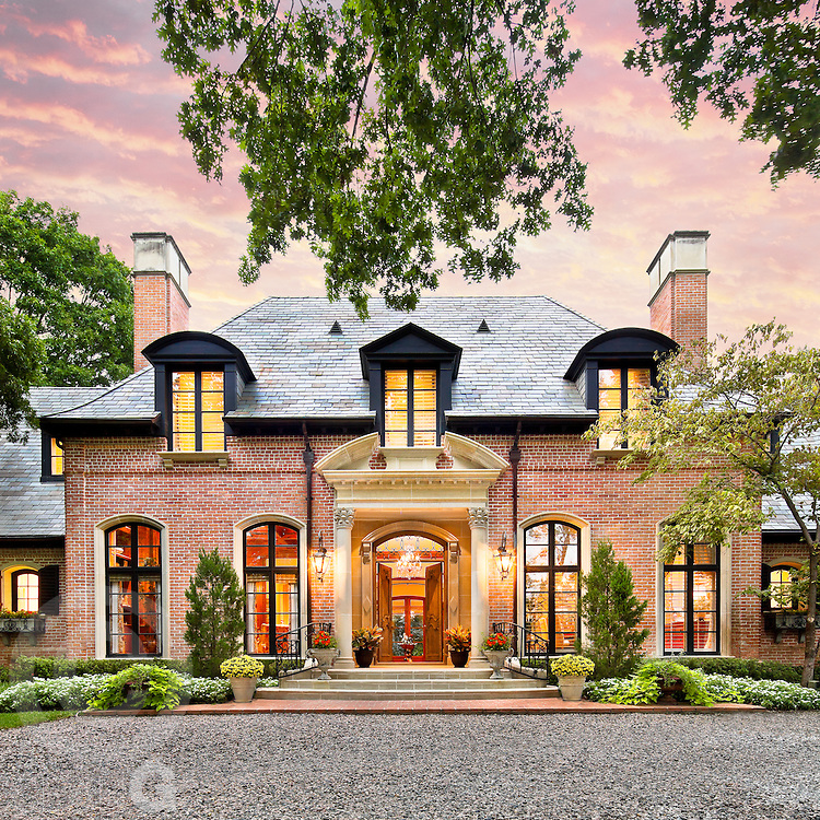 An elaborate french-inspired estate sits underneath a sunset sky.