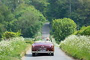 Motorist driving away in a stylish British made Alvis TD21 classic car along a country lane in The Cotswolds, England