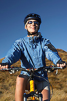 Woman sitting on bicycle in field