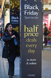 © Licensed to London News Pictures. 28/11/2019. LONDON, UK. A shopper outside the Debenhams department store which is promoting discounts in Oxford Street, the capital's busiest shopping area, on the eve of Black Friday.  The US phenomenon of discounts for Thanksgiving has now been adopted by many retailers in the UK with several offering discounts during the prior week, instead of on the day itself.  Critics question whether some discounts offered on the day are cheaper than at other times.  Photo credit: Stephen Chung/LNP
