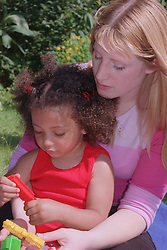 Portrait of teenage mother sitting in garden behind young daughter playing with stickle bricks,