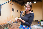 VSO ICS volunteer Josie Kearney learns about looking after ducklings in her host home. Volunteers stay with local families get the full experience. Lindi, Lindi region. Tanzania.