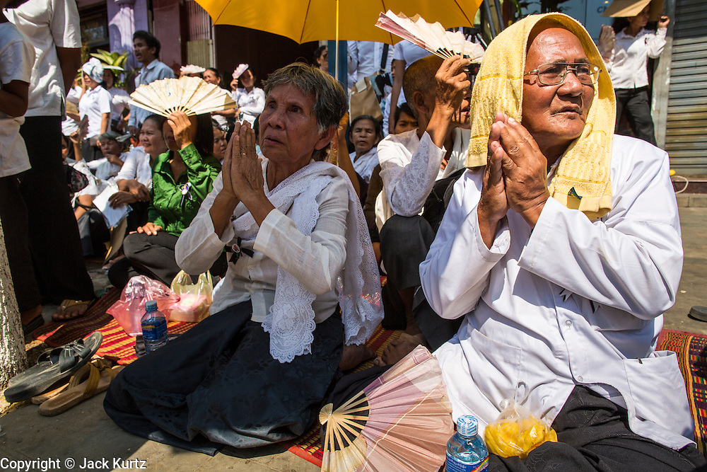 "04 FEBRUARY 2013 - PHNOM PENH, CAMBODIA: Mourners sit on the street in front of the National Museum during the cremation of King-Father Norodom Sihanouk in Phnom Penh. Norodom Sihanouk (31 October 1922 - 15 October 2012) was the King of Cambodia from 1941 to 1955 and again from 1993 to 2004. He was the effective ruler of Cambodia from 1953 to 1970. After his second abdication in 2004, he was given the honorific of ""The King-Father of Cambodia."" Sihanouk died in Beijing, China, where he was receiving medical care, on Oct. 15, 2012.    PHOTO BY JACK KURTZ"