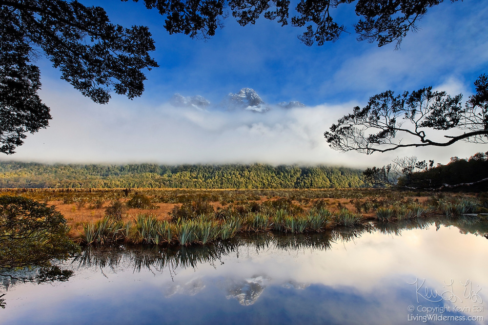 The summit of Mount Eglinton is barely visible over a thick cloud bank in Fiordland National Park, New Zealand. The mountain is reflected in Mirror Lake.