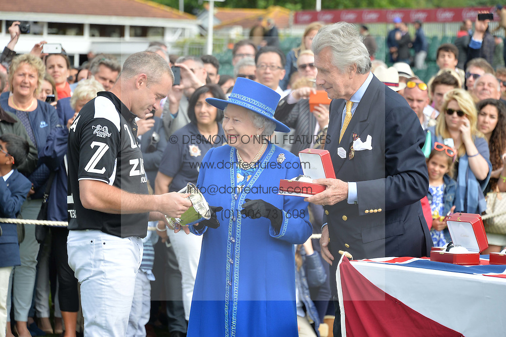 Left to right, LYNDON LEA receives the Cartier Queen's Cup from HM THE QUEEN and ARNAUD BAMBERGER at the Cartier Queen's Cup Final polo held at Guards Polo Club, Smith's Lawn, Windsor Great Park, Egham, Surrey on 15th June 2014.