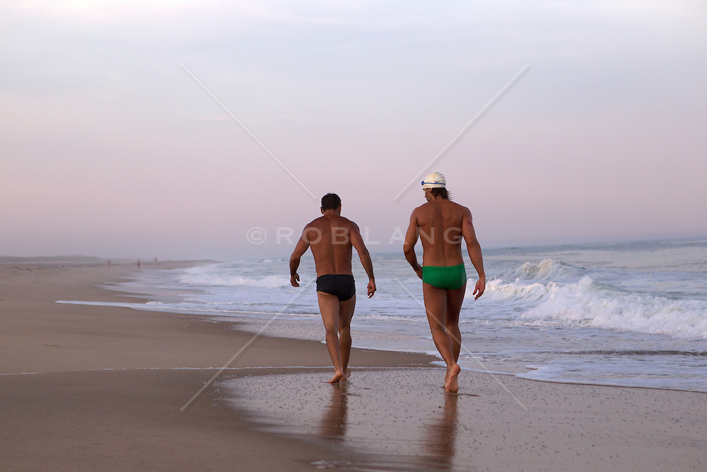 two men in speedo bathing suits walking down the beach at sunset in East Hampton, NY