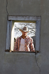 All American cowboy looking through an old adobe window in New Mexico