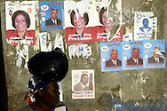 A woman walks near campaign posters in the Cite-Soliel neighborhood of Port-Au-Prince, Haiti February 1, 2006. Demonstrators were protesting the United Nations' plans to have voting stations for voters outside of Cite-Soliel due to security concerns. Photo by Keith Bedford