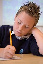 Teenager boy in class writing,
