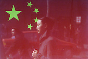 Pedestrians are reflected on a glass window protecting China's national flag in central Beijing February 28, 1998