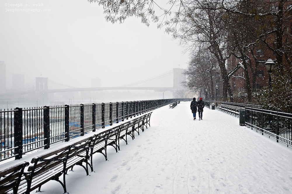 People walking in snowstorm on Brooklyn Heights Promenade, Brooklyn, NY, US