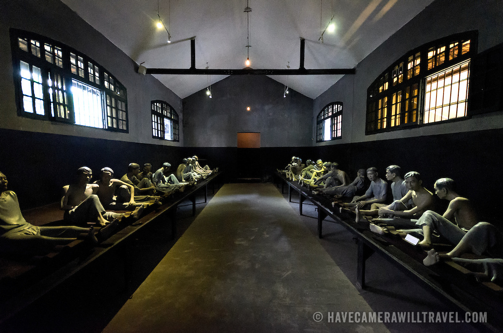 Plastic dummies demonstrate the conditions that inmates were kept in at Hoa Lo Prison. Prisoners were shackled by one leg into irons running the length of each side of the room. Hoa Lo Prison, also known sarcastically as the Hanoi Hilton during the Vietnam War, was originally a French colonial prison for political prisoners and then a North Vietnamese prison for prisoners of war. It is especially famous for being the jail used for American pilots shot down during the Vietnam War.
