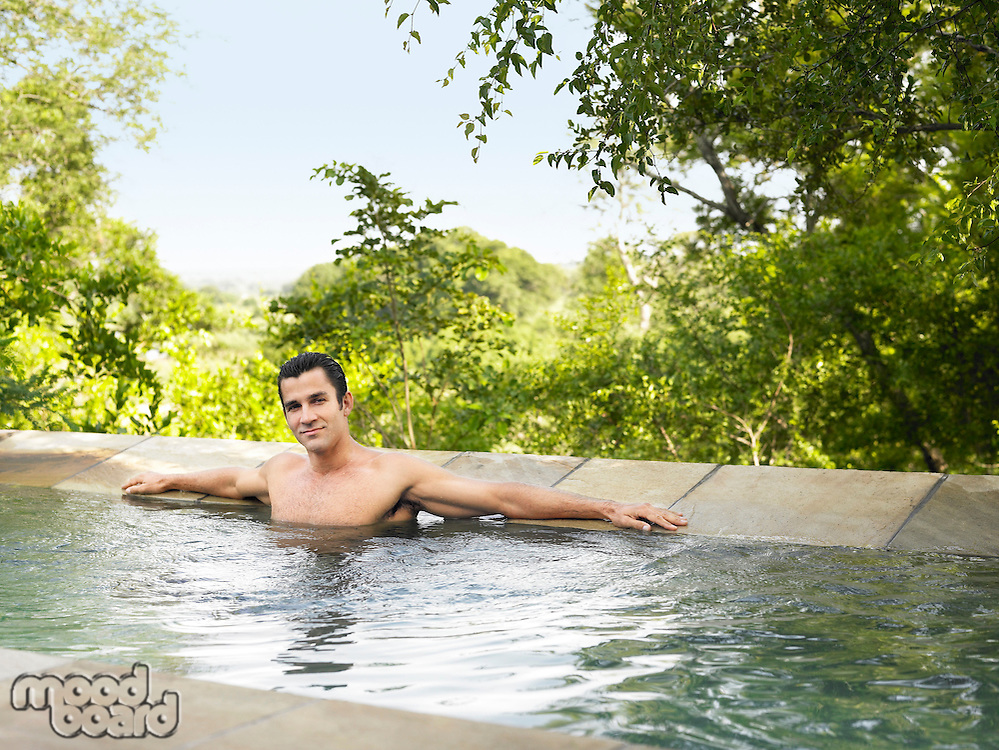 Portrait of mid adult man sitting in pool arms outstretched