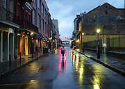 A woman walks in the middle of a street through the rain-soaked and deserted French Quarter of New Orleans in advance of Hurricane Katrina August 28, 2005.  Hundreds of thousands of New Orleans residents fled inland as Katrina strengthened into one of the fiercest U.S. storms ever seen and barreled toward the low-lying Gulf Coast city.