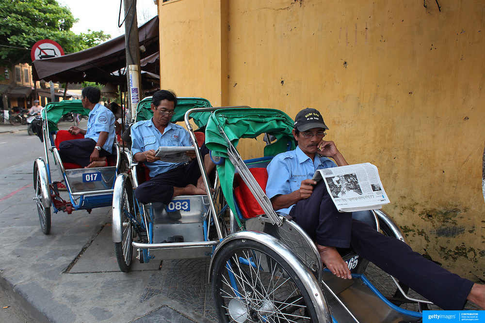 Cyclo drivers relax on a street corner in Hoi An, Vietnam. Hoi An is an ancient town and an exceptionally well-preserved example of a South-East Asian trading port dating from the 15th century. Hoi An is now a major tourist attraction because of its history. Hoi An, Vietnam. 5th March 2012. Photo Tim Clayton
