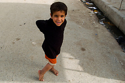 A young Iraqi boy stops to pose for the camera while playing in the street near a market area of Basra in March 2005