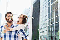 Happy man giving piggyback ride to woman in city