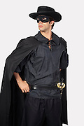 Young man dressed as Zorro against gray background
