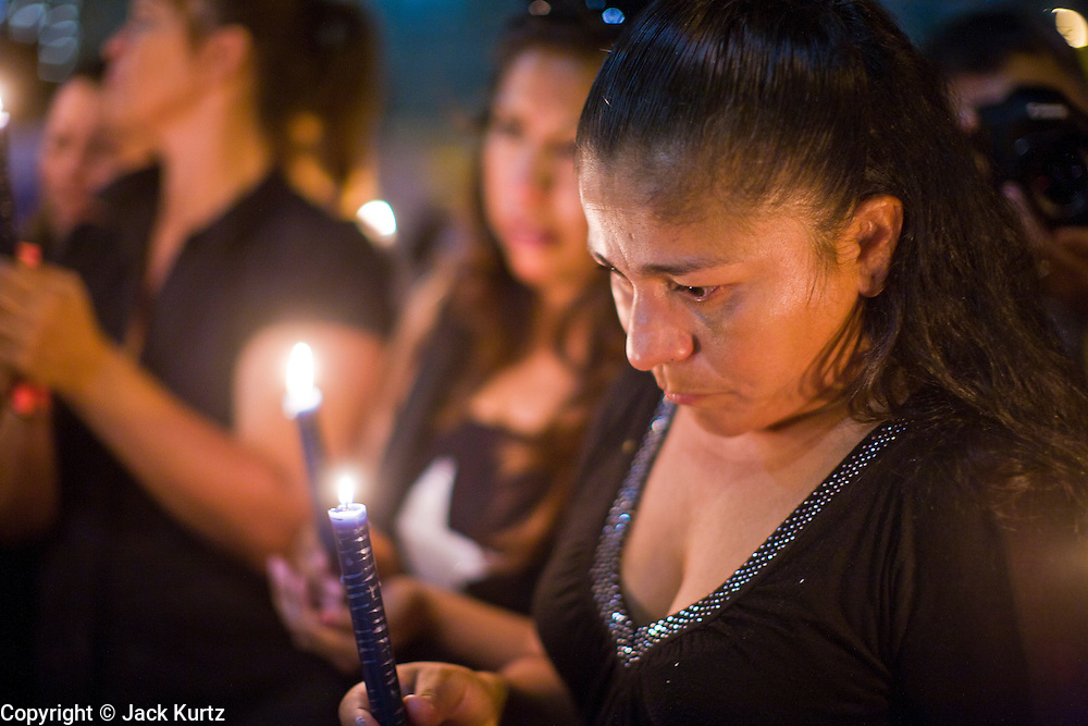 11 OCTOBER 2010 - PHOENIX, AZ: GEORGINA SANCHEZ, from Phoenix, and others participate in a candle light march around Phoenix police headquarters Monday night. About 300 people gathered at the Phoenix Police Department headquarters building Monday night to protest the shooting of Daniel Rodriguez and his dog. The officers responded to a 911 call made by Rodriguez' mother. A scuffle ensued when they arrived and Phoenix police officer Richard Chrisman shot Rodriguez, who was unarmed, and his dog. Chrisman then allegedly filed a false report about the event. He has been arrested on felony assault charges. The event has angered some in the Latino community and they have held a series of protests at the police headquarters. They want Chrisman charged with murder.    Photo by Jack Kurtz