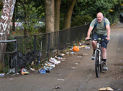 © Licensed to London News Pictures. 27/08/2019. London, UK. A man cycles past rubbish left along a canal tow path in Notting Hill, west London, in the aftermath of the 2019 Notting Hill carnival. The two day event is the second largest street festival in the world after the Rio Carnival in Brazil, attracting over 1 million people to the streets of West London. Photo credit: Ben Cawthra/LNP