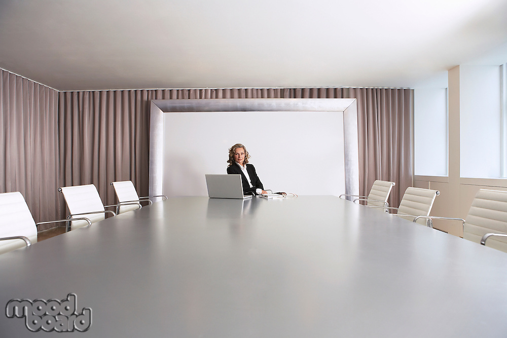 Female Business Executive Sitting in Boardroom with Laptop