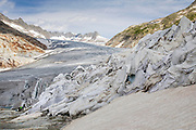 Tourists at the Rhone Glacier in Switzerland. After a winter with record amounts of snow, most of it was gone when this imae was taken on July 14th 2018, exposing the darker ice. While snow is a brilliant reflector of the energy from the sun, the darker ice absorbs the energy instead, accelerating the melting of the glacier. The color and darkness of glacier ice vary all over the world, depending on build-up of pollution, age of the ice, particles picked up by the ice and by microorganisms in the ice. The glacier ice is however rarely white as snow. With shorter winters and vanishing snow cover, the melting of the glaciers is accelerating.<br /> The Rhone Glacier now melts more than 70 centimeters in thickness every week during the summer months. Between 1996 and 2006, an estimated 0.9 billion cubic metres of water melted yearly from the Swiss glaciers. That number is likely much higher today. Switzerland just had the hottest July since 1921, and the rivers are running at record low levels.