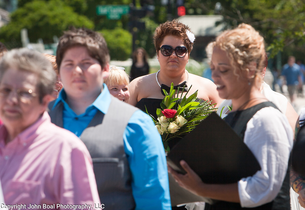 Liberty Manos, center (with flowers), of Akron, Ohio, listens as Officiant, Tiffany Newman, right, marries twenty-five gay couples in front of the Supreme Court of the United States, on June 21, 2013.  The couples traveled to Washington on the C-Bus of Love to get married en masse the week before decisions are expected to be made on the Defense of Marriage Act (DOMA) and Proposition 8.   John Boal photography