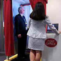 A delegate poses for a passport photo at a post office booth during the Conservatives Party Conference at Manchester Central.