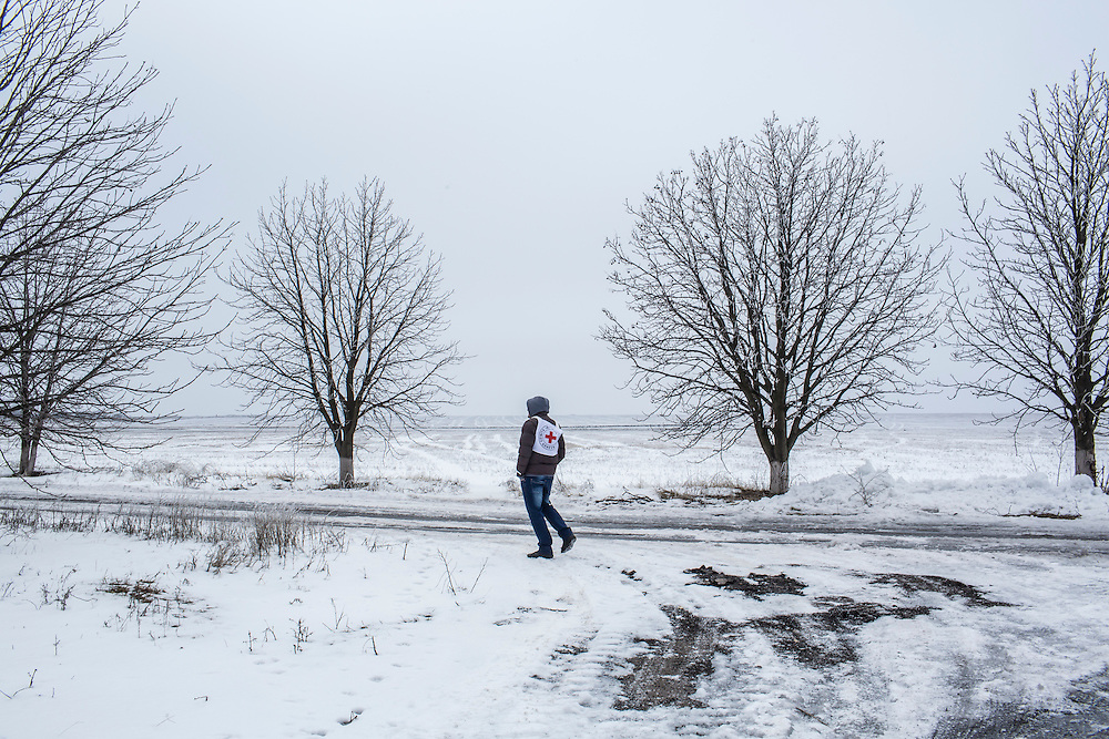 MNOGOPOLYE, UKRAINE - JANUARY 24, 2015: Sasha Lokin, who worked with the International Committee of the Red Cross to deliver humanitarian aid to Mnogopolye, Ukraine, on a road by a field at the edge of the village. ICRC aid deliveries are planned for the area approximately once per month, and supply food and hygiene items for more than one thousand people. CREDIT: Brendan Hoffman for The New York Times