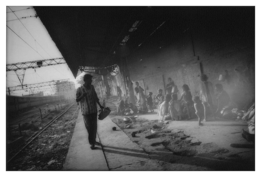 Lowest of the low: Commuter eyes untouchable (Dalit) squatters who have colonized abandoned train platform, Howrah Station, Calcutta, India.