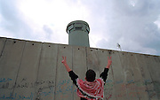 A Palestinian protester flashes the victory sign before an Israeli army outpost along the 8 meter high Ie concrete wall, part of the controversial Israeli security barrier built by Israel to separate the nation from the West Bank, near the Palestinian town of Qalqilya, November 9, 2003. Foreign activists together with Palestinian demonstrators  protested against the wall on the anniversay of the fall of the Berlin Wall.Israel says it is building the vast barrier as a security measure to keep out bombers while Palestinians say it steals their land. Photo by Heidi Levine/Sipa Press).