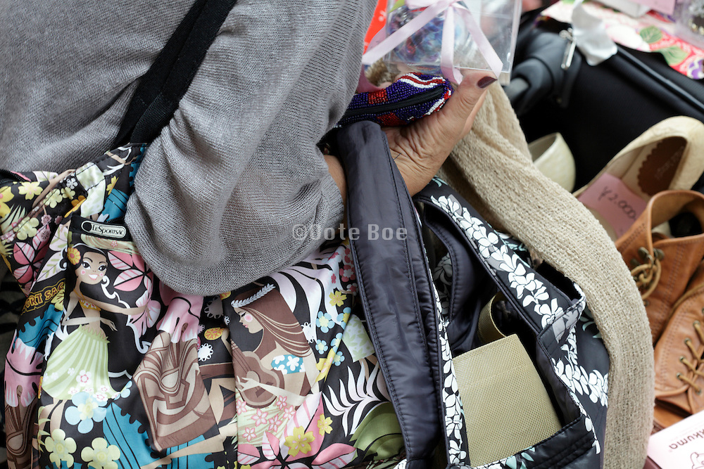 close up of woman holding several bags and purchases at a flea market